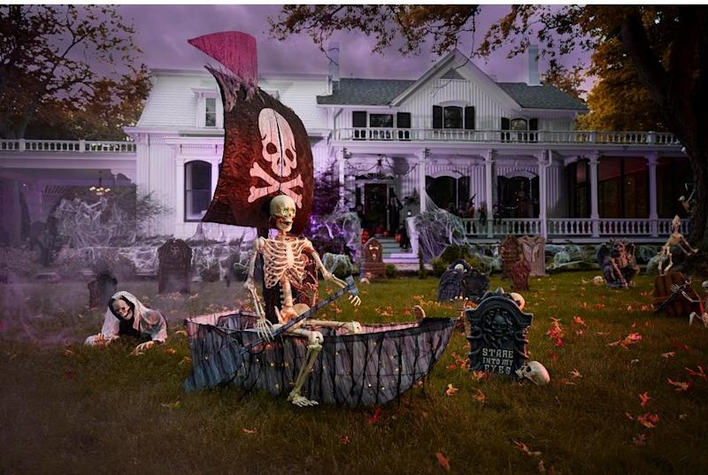 A faux pirate ship halloween decoration in the front yard of a white house after dark