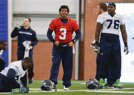 Seattle Seahawks quarterback Russell Wilson smiles during stretches while teammate Russell Okung (R) looks on at their NFL Super Bowl XLVIII football practice in East Rutherford, New Jersey, January 30, 2014. REUTERS/Shannon Stapleton