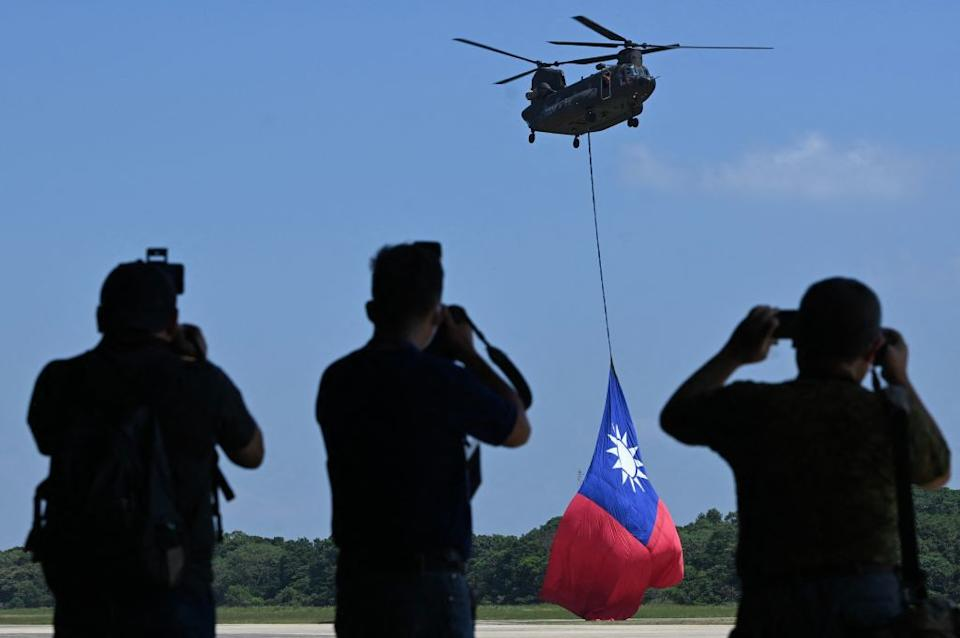 A US-made CH-47 helicopter flies an 18-meter by 12-meter national flag at a military base in Taoyuan.