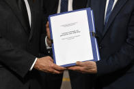 """FILE - In this March 26, 2021 file photo, the report on the France's role in 1994's Rwandan genocide is given by Historian and Commission chief, Vincent Duclert to French President Emmanuel Macron, at the Elysee Palace, in Paris. France's role before and during 1994's Rwandan genocide was a """"monumental failure"""" that the country must face, the lead author of a sweeping report commissioned by President Emmanuel Macron said, as the country is about to open its archives from this period for the first time to the public. (Ludovic Marin/Pool photo via AP, File)"""