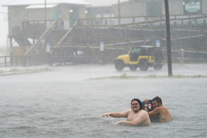 Image: People play in a flooded parking lot at Navarre Beach, Tuesday, Sept. 15, 2020, in Pensacola Beach, Fla. (Gerald Herbert / AP)