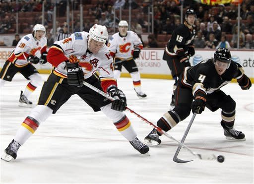 Anaheim Ducks defenseman Cam Fowler, right, tries to hit the puck away from Calgary Flames defenseman Jay Bouwmeester, left, in the first period of an NHL hockey game in Anaheim, Calif., on Monday, Feb. 6, 2012. (AP Photo/Christine Cotter)
