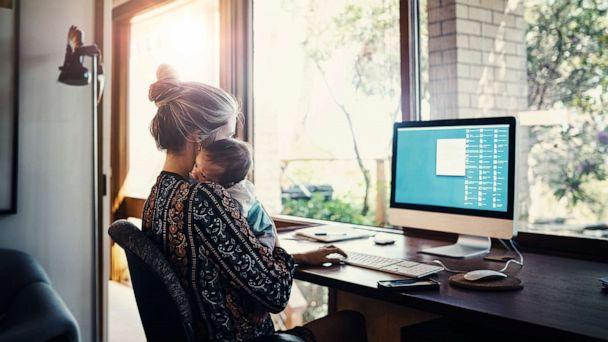 PHOTO: A woman holds a child while using a computer in this stock photo. (STOCK PHOTO/Getty Images)