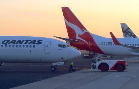 FILE PHOTO - Workers are seen near Qantas Airways, Australia's national carrier, Boeing 737-800 aircraft on the tarmac at Adelaide Airport