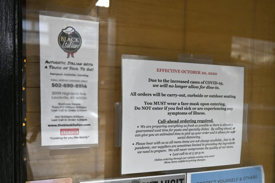 Signs on the door of The Black Italian restaurant and catering service showing the COVID-19 restrictions, in Louisville, Ky., Thursday, Dec. 3, 2020. The restaurant's owners, Paula and Anthony Hunter cannot have in person dining, and are hoping for another round of federal aid to hang on until vaccines can conquer the virus. (AP Photo/Timothy D. Easley)
