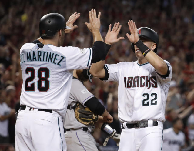 Arizona Diamondbacks' J.D. Martinez (28) high-fives Jake Lamb (22) after they scored on a two-run triple by A.J. Pollock during the eighth inning of the National League wild-card game against Colorado. (AP)