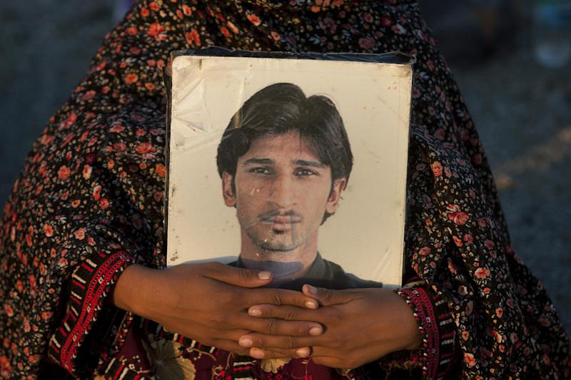 In this Tuesday, Nov. 19, 2013, photo, a Pakistani woman, holds a photograph of a relative, who was allegedly abducted by Pakistani security forces, as she and others march toward Karachi, in Gadani, Pakistan. Baluch is one of roughly two dozen activists making the journey on foot from Quetta, the capital of southwest Baluchistan province, to the southern port city of Karachi to protest thousands of people who have gone missing over the years as Pakistani authorities have battled a separatist insurgency in Baluchistan. (AP Photo/Shakil Adil)