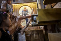 Coptic Orthodox christians light candles during Easter mass, at Holy Cross Church in Cairo, Egypt, Saturday, May 1, 2021. Orthodox Christians around the world celebrate Easter on Sunday, May 2. (AP Photo/Nariman El-Mofty)