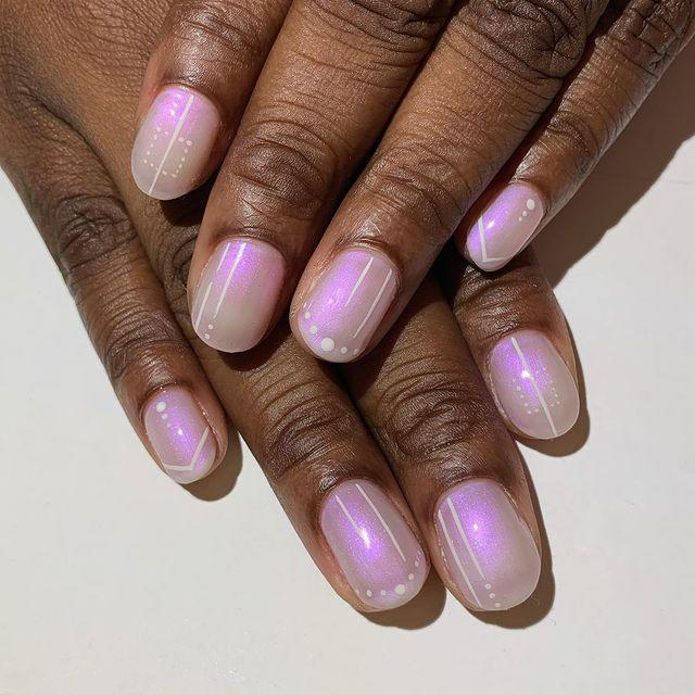 "<p>The cool thing about <a href=""https://www.cosmopolitan.com/style-beauty/beauty/g8264828/holographic-nail-polish/"" rel=""nofollow noopener"" target=""_blank"" data-ylk=""slk:iridescent nail polish"" class=""link rapid-noclick-resp"">iridescent nail polish</a> is you really don't need to add a whole bunch to it to make it nail art. The thin white lines and tiny dots look like shine marks on this <a href=""https://taupecoat.com/collections/shop-all/products/a-little-bubbly"" rel=""nofollow noopener"" target=""_blank"" data-ylk=""slk:cotton candy-colored polish"" class=""link rapid-noclick-resp"">cotton candy-colored polish</a>.</p><p><a href=""https://www.instagram.com/p/CDU0KQYDV_B/?utm_source=ig_embed&utm_campaign=loading"" rel=""nofollow noopener"" target=""_blank"" data-ylk=""slk:See the original post on Instagram"" class=""link rapid-noclick-resp"">See the original post on Instagram</a></p>"