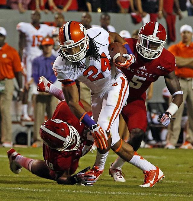 Clemson running back Zac Brooks (24) tries to break away from North Carolina States' Robert Caldwell (48) with NC State's Rodman Noel (5) nearby during the first half of an NCAA college football game in Raleigh, N.C., Thursday, Sept. 19, 2013. (AP Photo/Karl B DeBlaker)