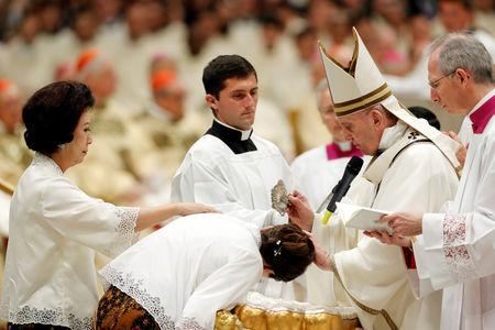 Pope Francis baptizes a faithful during the Easter vigil Mass in Saint Peter's Basilica at the Vatican, April 20,2019. REUTERS/Remo Casilli
