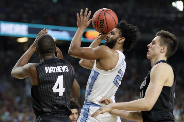 FILE - In this April 3, 2017, file photo, North Carolina's Joel Berry (2) takes a shot between Gonzaga's Jordan Mathews (4) and Zach Collins during the first half in the finals of the Final Four NCAA college basketball tournament, in Glendale, Ariz. North Carolina defeated Gonzaga 71-65. Berry was named MVP. (AP Photo/Mark Humphrey, File)