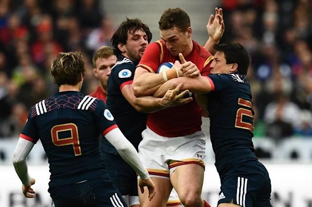Wales' wing George North (C) is tackled during a Six Nations match against Wales at the Stade de France in Saint-Denis, outside Paris, on March 18, 2017 (AFP Photo/CHRISTOPHE SIMON)