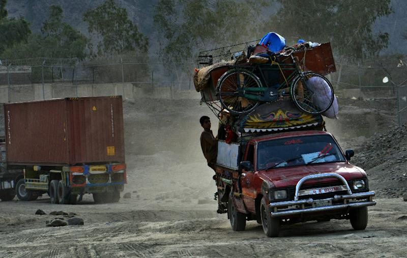 Afghan refugees travelling with their posessions cross the Pakistan-Afghanistan border at the Torkham crossing point on September 7, 2016