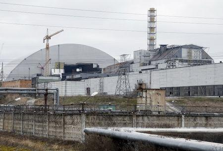 A general view shows a containment shelter for the damaged fourth reactor (R) and the New Safe Confinement (NSC) structure (L) at the Chernobyl Nuclear Power Plant, Ukraine, March 23, 2016. REUTERS/Gleb Garanich
