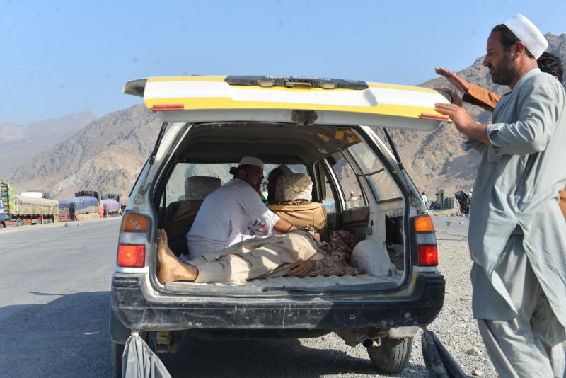 Men carry a dead body with a civilian vehicle in Momandara district of Nangarhar province Afghanistan Tuesday Sept. 11 2018. A suicide bomber detonated his explosives-filled vest among a group of people protesting a local police commander in eastern A