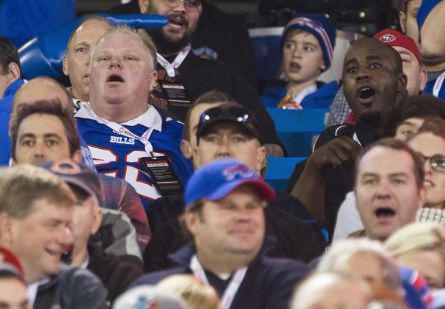 Toronto Mayor Rob Ford, left, and his driver Jerry Agyemang, right, watch the Buffalo Bills play the Atlanta Falcons during the first half of NFL football action in Toronto, Sunday December 1, 2013. (AP Photo/The Canadian Press, Mark Blinch)