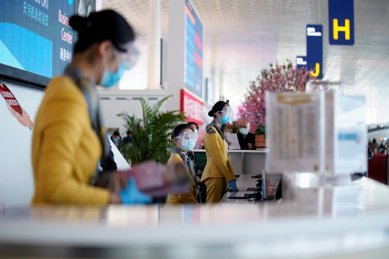 Staff members wearing face masks and goggles are seen at a counter at the Wuhan Tianhe International Airport