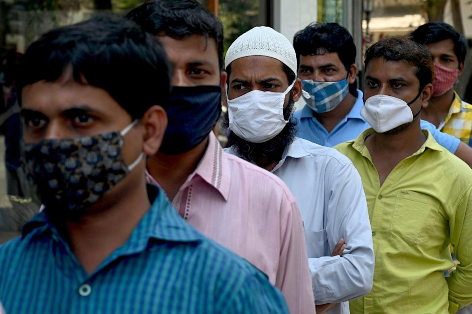 <p>People wait in a queue to get a Rapid Antigen Testing (RAT) at a roadside market following restrictions imposed by the state government</p> (AFP via Getty Images)