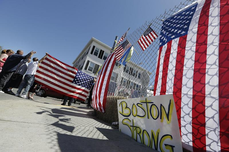 Protesters gesture and hold a flag outside the Graham, Putnam, and Mahoney Funeral Parlors in Worcester, Mass., Monday, May 6, 2013, where the body of killed Boston Marathon bombing suspect Tamerlan Tsarnaev is being prepared for burial. Funeral director Peter Stefan has pleaded for government officials to use their influence to convince a cemetery to bury Tsarnaev, but so far no state or federal authorities have stepped forward. (AP Photo/Elise Amendola)