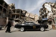 A woman walks past a vehicle parked near damaged buildings in Douma