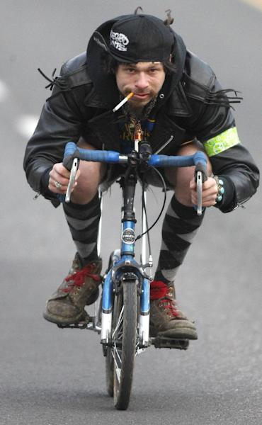 """Dan Oviatt, known as """"Captain America,"""" rides his mini bike during a three-day Mini Bike Winter Olympics Sunday, Feb.19, 2012, in Portland, Ore. """"Zoobombers"""" are known for riding pint-sized kids' bikes at breakneck speed down steep streets in Portland. (AP Photo/Rick Bowmer)"""