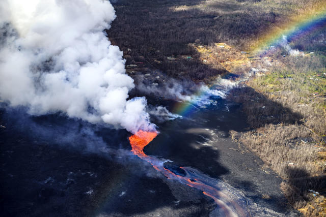<p>The Kilauea volcano on Hawaii's Big Island erupted on May 3, 2018, and has continued to send lava over the surrounding neighborhoods. (Photo: CJ Kale/Caters News) </p>