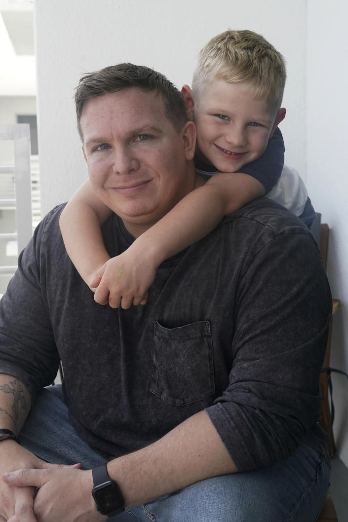Associated Press investigative reporter James LaPorta and his son Joel, 5, sit at their home, Tuesday, Sept. 7, 2021, in Boca Raton, Fla. LaPorta recalls a boy he encountered in Afghanistan back in 2013 while serving as a Marine. (AP Photo/Marta Lavandier)