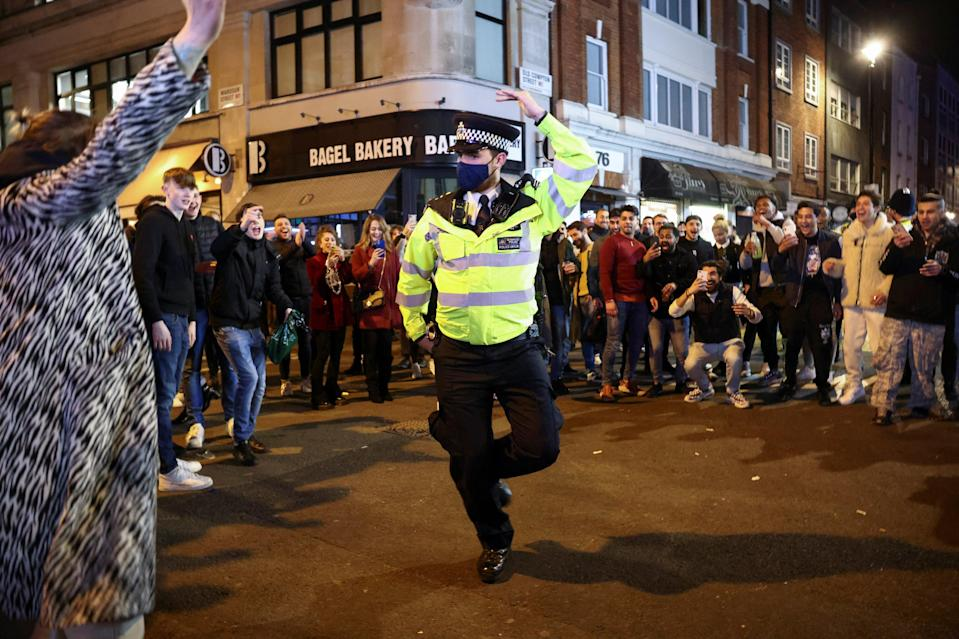 A policeman dances with people partying along a street in SohoREUTERS