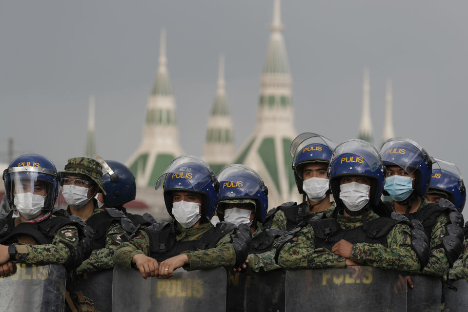 Police officers wearing face masks stand guard as they secure the road leading to the House of Representatives where President Rodrigo Duterte will deliver his 5th State of the Nation Address (SONA) on Monday, July 27, 2020, in Manila, Philippines. (AP Photo/Aaron Favila)