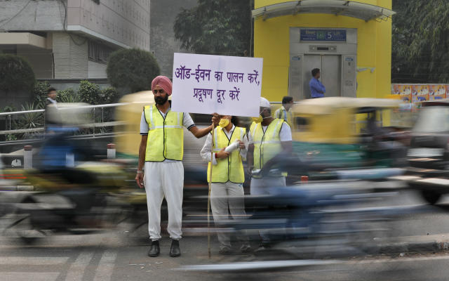 Volunteers wear pollution masks as they stand at a busy crossing with the banner saying obey odd and even, remove pollution, in New Delhi, India, Nov. 4, 2019. (Photo: Manish Swarup/AP)