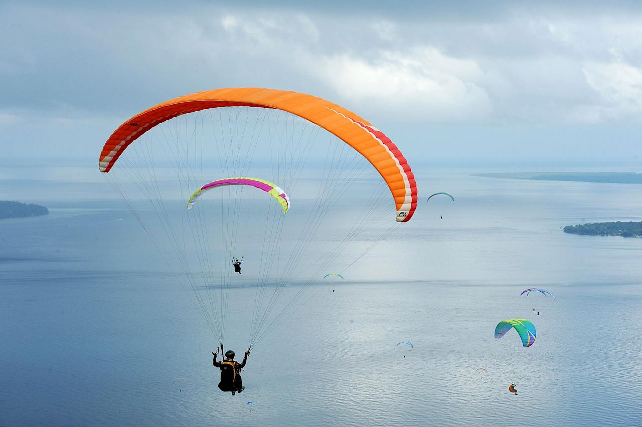 <p>Paragliders fly during the Paragliding Accuracy World Cup 1st Series 2017 at Mount Tumpa on March 17, 2017, in Manado, Indonesia. (Robertus Pudyanto/Getty Images) </p>
