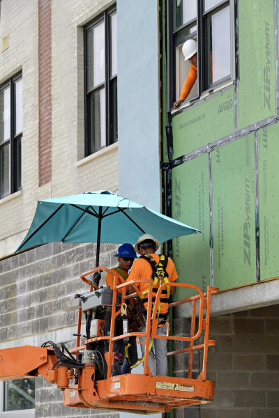 A construction crew keeps out of the sun with a sun umbrella on their boom lift as they work on an apartment building along S. Jefferson Davis Parkway in New Orleans, La. Tuesday, Aug. 13, 2019. National Weather Service issued a heat advisory for the New Orleans area Tuesday. 