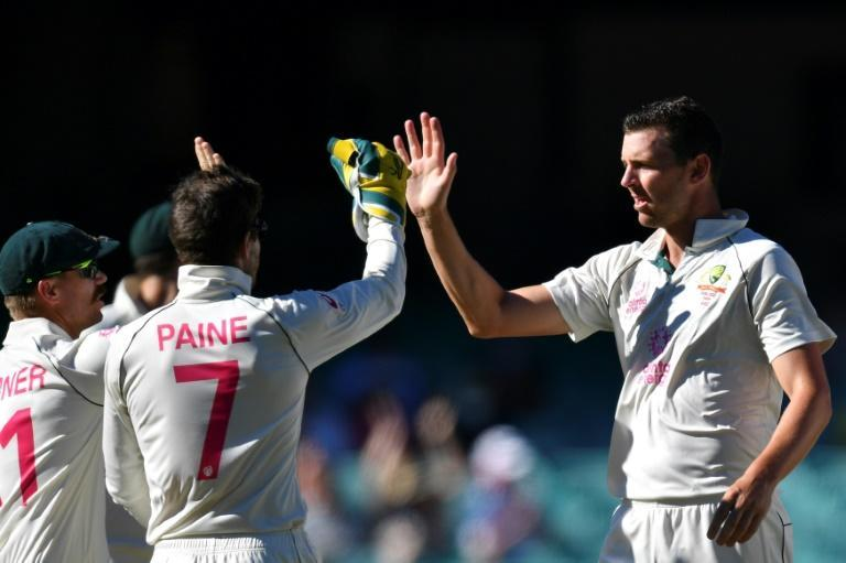 Australia's Josh Hazlewood (right) celebrates with teammates David Warner and captain Tim Paine after taking the wicket of India's Shubman Gill
