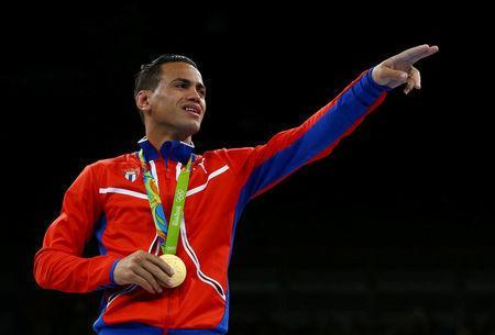 FILE PHOTO: 2016 Rio Olympics - Boxing - Victory Ceremony - Men's Bantam (56kg) Victory Ceremony - Riocentro - Pavilion 6 - Rio de Janeiro, Brazil - 20/08/2016. Gold medallist Robeisy Eloy Ramirez Carrazana (CUB) of Cuba gestures while posing with his medal. REUTERS/Peter Cziborra/File photo