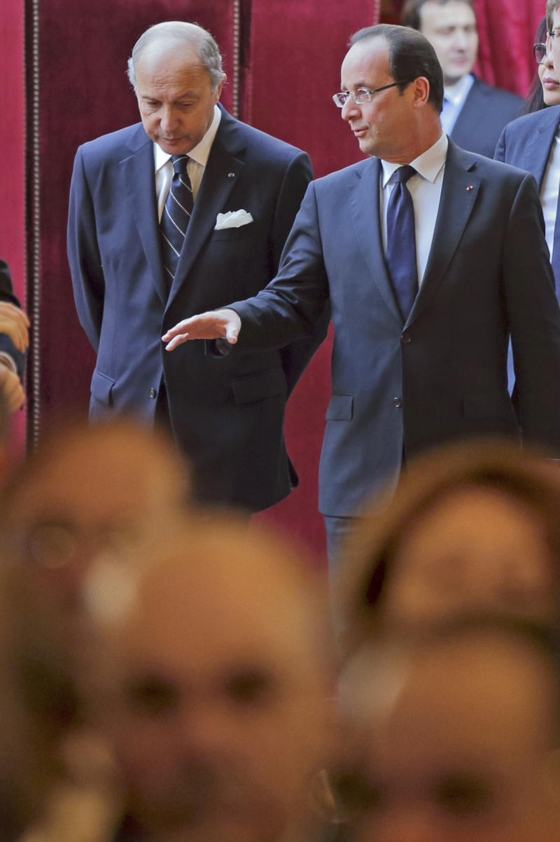 French President Francois Hollande , righ, talks with his foreign minister Laurent Fabius as they arrive for a New Year wishes ceremony for diplomats at the Elysee Palace in Paris, Friday  Jan. 11, 2013.(AP Photo/Philippe Wojazer/Pool)
