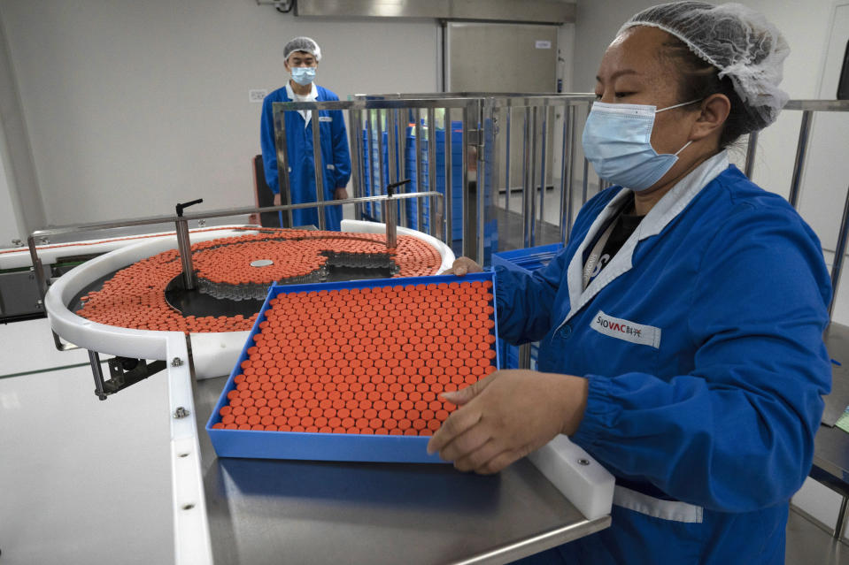 FILE - In this Sept. 24, 2020, file photo, a worker feeds vials for production of SARS CoV-2 Vaccine for COVID-19 at the SinoVac vaccine factory in Beijing. China said on Friday, Oct. 9, 2020, that it is joining the COVID-19 vaccine alliance known as COVAX. (AP Photo/Ng Han Guan, File)