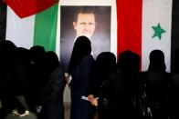 FILE PHOTO: Women stand as they wait their turn to cast the votes inside a polling station during the parliamentary elections in Douma