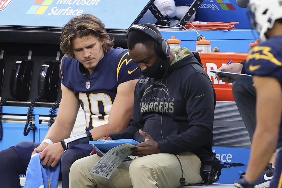 Los Angeles Chargers quarterback Justin Herbert (10) gets instruction from quarterbacks coach Pep Hamilton during an NFL football game against the Las Vegas Raiders, Sunday, Nov. 8, 2020, in Inglewood, Calif. The most recognizable trend in hiring NFL head coaches has been to target young, innovative offensive teachers with a track record of developing quarterbacks. (AP Photo/Peter Joneleit)