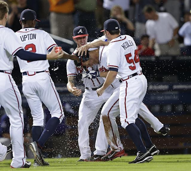 Atlanta Braves shortstop Andrelton Simmons, second from right, is mobbed by teammates Kris Medlen, right, and Jordan Schafer (17) after driving in the game-winning run with a triple in the 10th inning of a baseball game against the Colorado Rockies in Atlanta, Monday, July 29, 2013. Atlanta won 9-8. (AP Photo/John Bazemore)