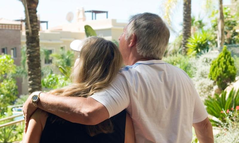 A newly retired couple standing on the balcony of their new home in Spain