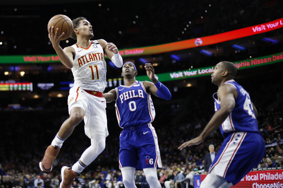 Atlanta Hawks' Trae Young, left, goes up to shoot against Philadelphia 76ers' Josh Richardson, center, and Al Horford during the first half of an NBA basketball game, Monday, Feb. 24, 2020, in Philadelphia. (AP Photo/Matt Slocum)