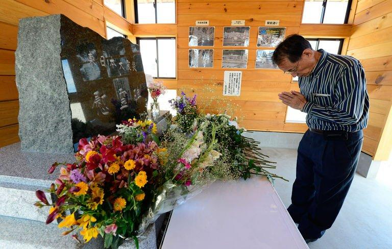 """A tourist prays for victims in front of a monument in Rikuzentakata, Japan, on July 20, 2013. Though the city was nearly wiped off the map by the 2011 tsunami, visitors are flocking back to see the devastation, the latest example of a phenomenon dubbed """"dark tourism"""" where holidaymakers pay to witness the aftermath of others' misery"""
