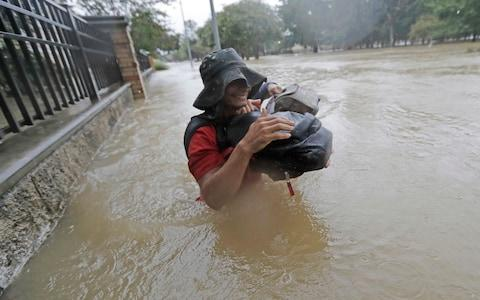 Residents in Houston wade through floodwaters - Credit: AP Photo/David J. Phillip