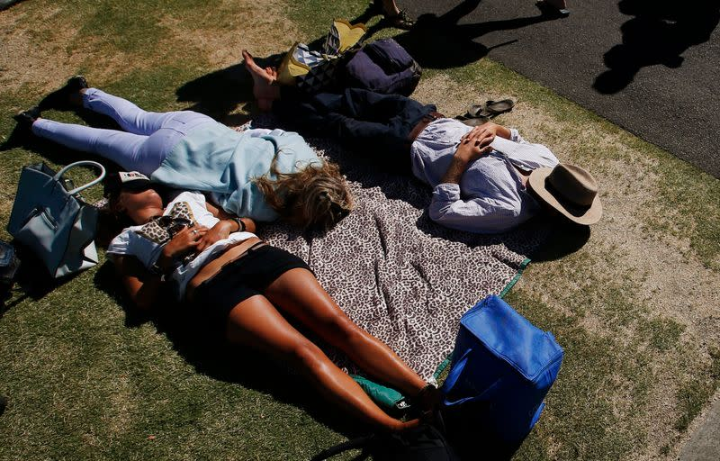 Tennis spectators rest on the grass on the first day of the Australian Open tennis tournament in Melbourne