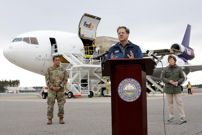 New Hampshire Gov. Chris Sununu, center, speaks to reporters, flanked by state National Guard Maj. Gen. David Mikolaities, left, and Sen. Jeanne Shaheen, D-N.H., as pallets containing personal protective equipment are unloaded from a FedEx cargo plane April 12 at Manchester-Boston Regional Airport in New Hampshire.