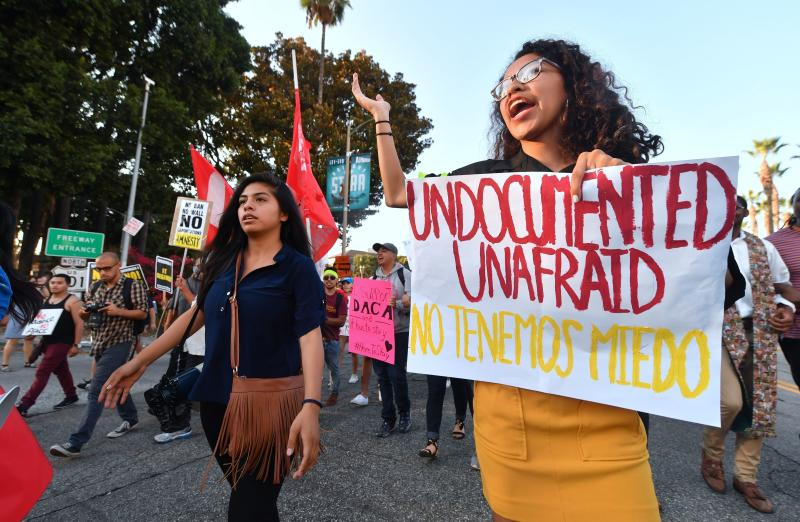 Young immigrants, activists and supporters of the DACA program march through downtown Los Angeles on Tuesday. (FREDERIC J. BROWN via Getty Images)