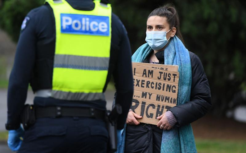 A woman with a sign speaks to police during a planned anti-lockdown protest - ERIK ANDERSON/EPA-EFE/Shutterstock