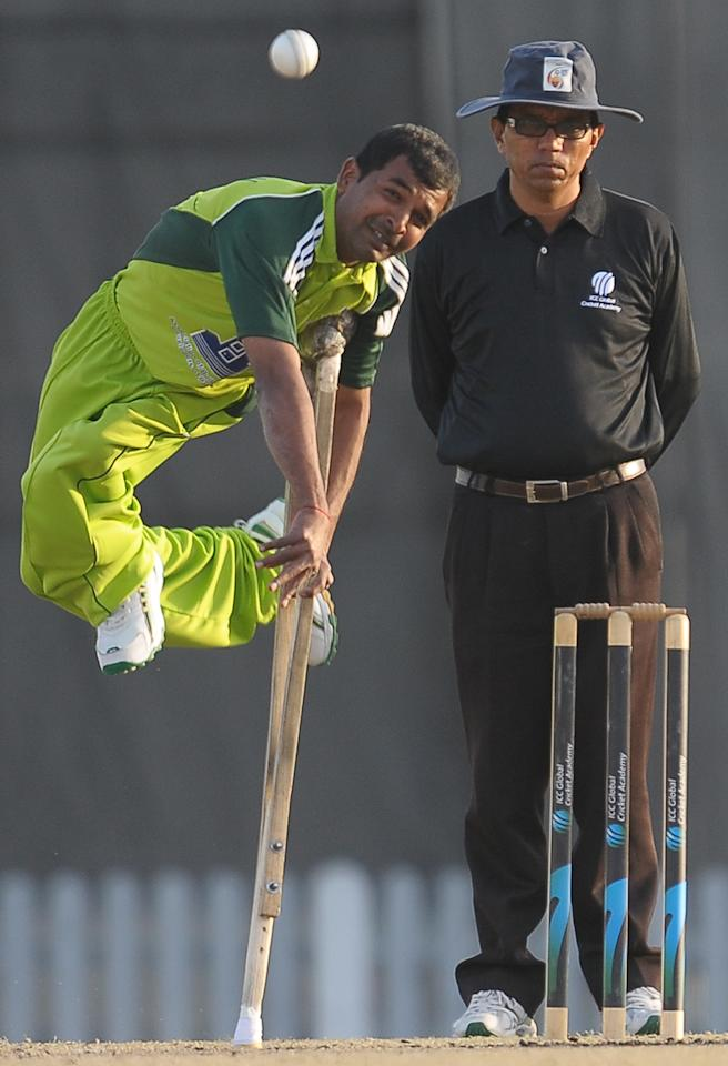 Pakistan disabled cricketer Farhan Saeed (L) delivers the ball during the T20 match between England Disaballity team and Pakistan Disaballity team at the ICC Global Cricket Academy (ICC GCA) in Dubai Sports City on February 11, 2012. Cricketers with disabilities from Pakistan and England promise to defy all odds during their ground-breaking series, hoping it could set examples for such other people in life. AFP PHOTO/ LAKRUWAN WANNIARACHCHI (Photo credit should read LAKRUWAN WANNIARACHCHI/AFP/Getty Images)