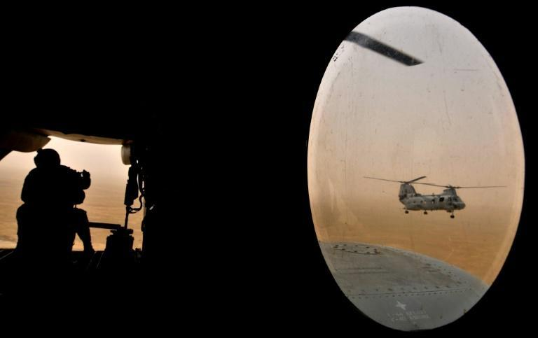 A US soldier (L) sits in the rear of a Marine Chinook helicopter while flying over Helmand province, southwest of Kabul on May 3, 2008 -- in the first decade of the war that US President Joe Biden now says he will end without conditions